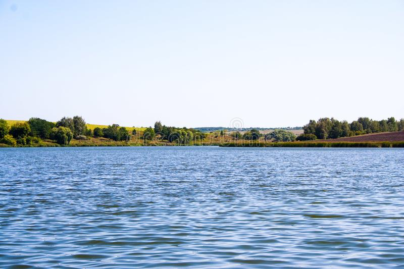 August calm lake. Sunny cloudless day in August, a calm lake, a plowed field, green trees and reeds on the opposite shore of the lake royalty free stock images