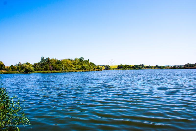 August calm lake. Sunny cloudless day in August, a calm lake, a plowed field, green trees and reeds on the opposite shore of the lake stock photos