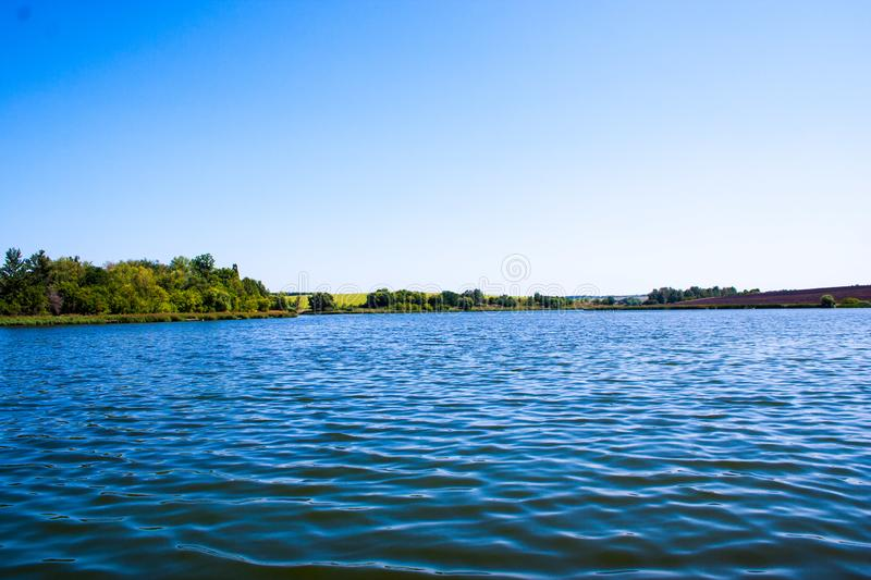 August calm lake. Sunny cloudless day in August, a calm lake, a plowed field, green trees and reeds on the opposite shore of the lake royalty free stock photo