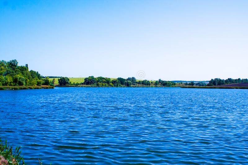 August calm lake. Sunny cloudless day in August, a calm lake, a plowed field, green trees and reeds on the opposite shore of the lake royalty free stock photos