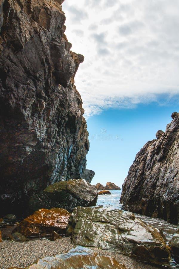 Sunny day beach tall rock canyon stock image