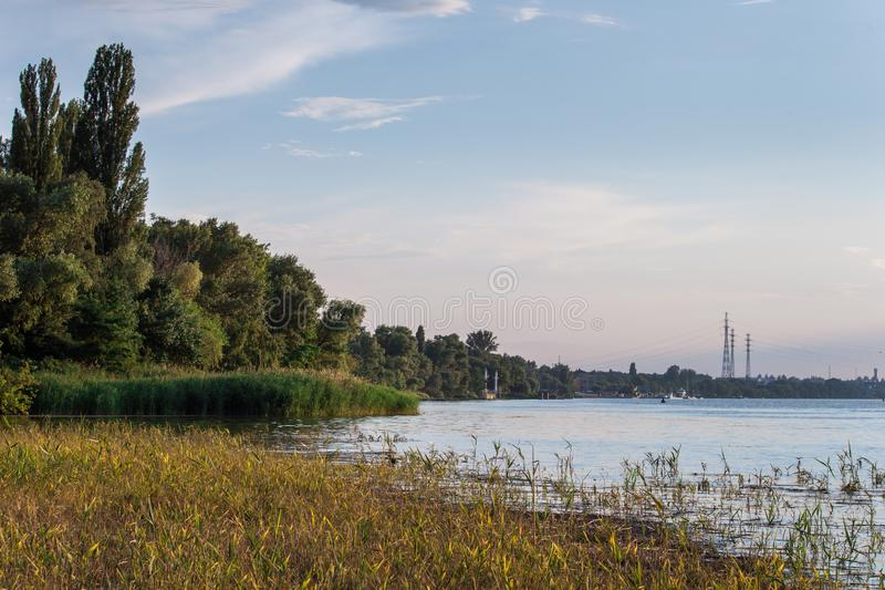 Sunny day on a calm river with bulrushes in summer. Nova Kakhovka, Ukraine. high-voltage power lines at sunset stock photo