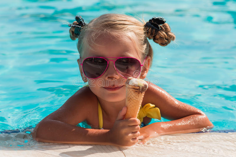 On a sunny day the girl in sunglasses with ice cream relaxing in the pool royalty free stock image