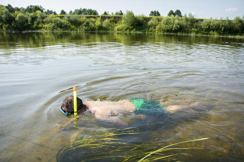 In summer, a man in a mask and a tube in clear water swim along stock image