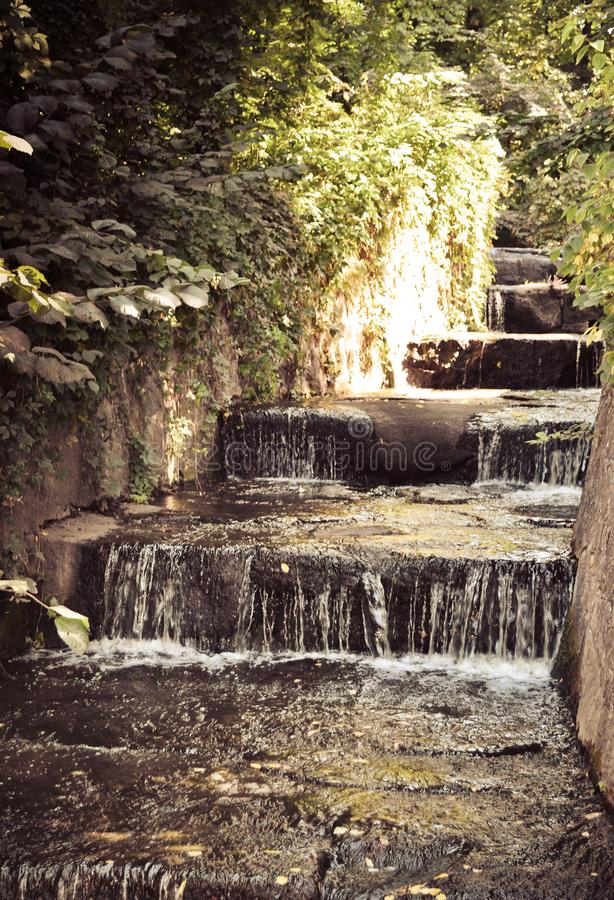 A sunny day is reflected in a babbling brook. A sunny day spent with Sofievsky Park. A softly gurgling stream runs down the steps stock photo