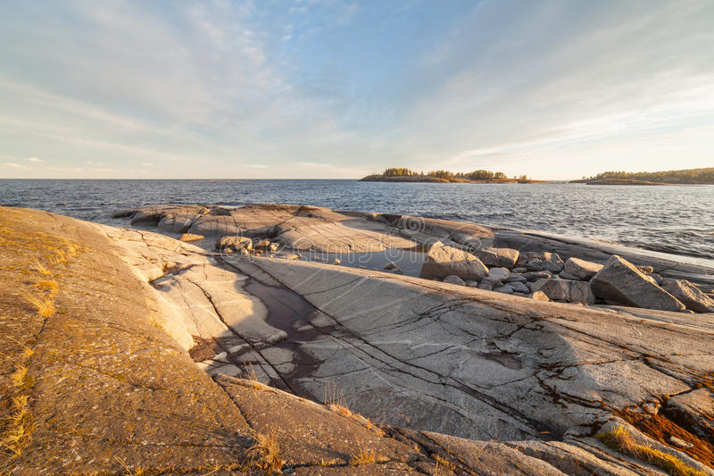Sunny day on the rocky shore of the lake. stock image