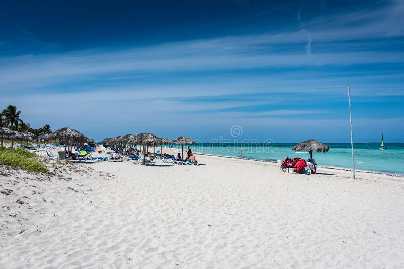 Sunny Day at Varadero Beach. Varadero, Cuba / March 17, 2016: Resort guests enjoying shade of grass topped umbrellas at the beach royalty free stock images