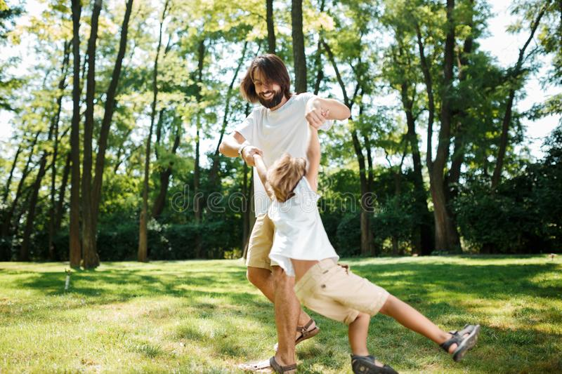 Sunny day young dark-haired father and his little son in white t shirts having fun and playing outdoor.  royalty free stock images