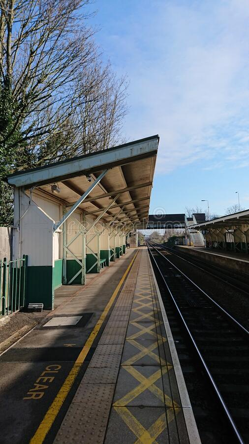 Sunny but deserted commuter train station royalty free stock photography