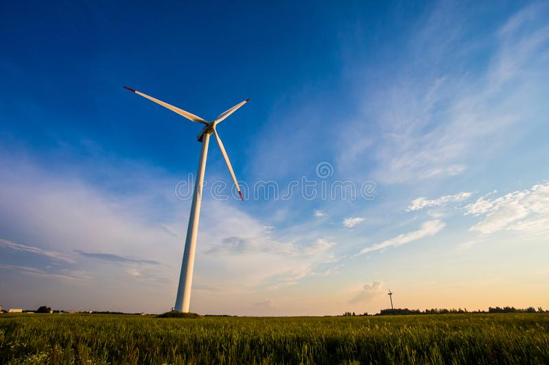Sunny evening in countryside. Wind turbine in blue sky background. Renewable energy concept stock image