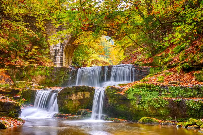 Natural Rapids of a Waterfall and Autumn Forest stock photos