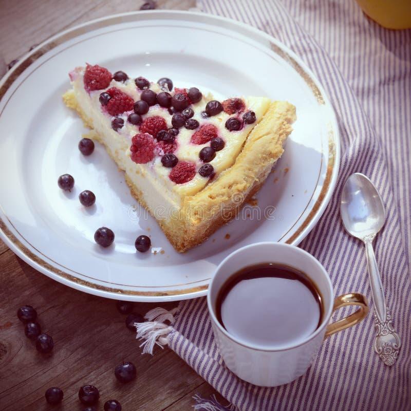 Sunny Foto mit einem Morgenfrühstück in der rustikalen Art Käsekuchenhimbeeren und -blaubeeren auf Holztisch quadrat lizenzfreie stockfotos