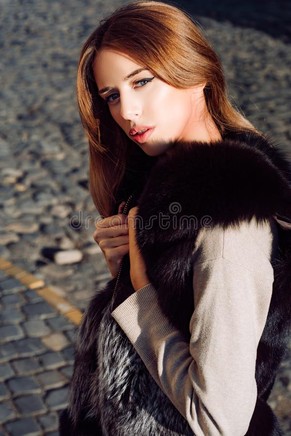 Sunny girl. Fall fashion. Enjoy warmth. Woman makeup enjoy sunny day outdoors. Fall outfit. Modern fashion outfit. Autumn season. Pretty woman in furry vest royalty free stock photos