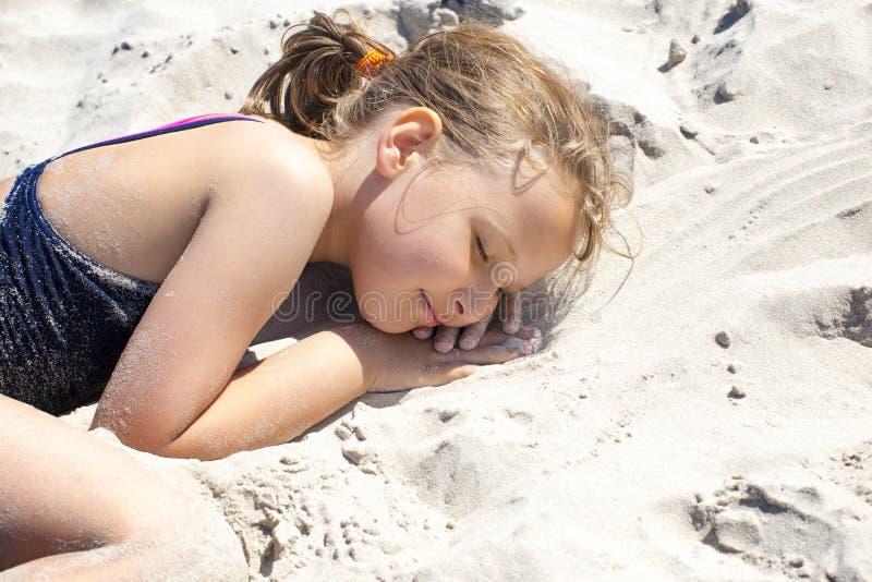 Sunny Girl Laying i sand royaltyfri bild