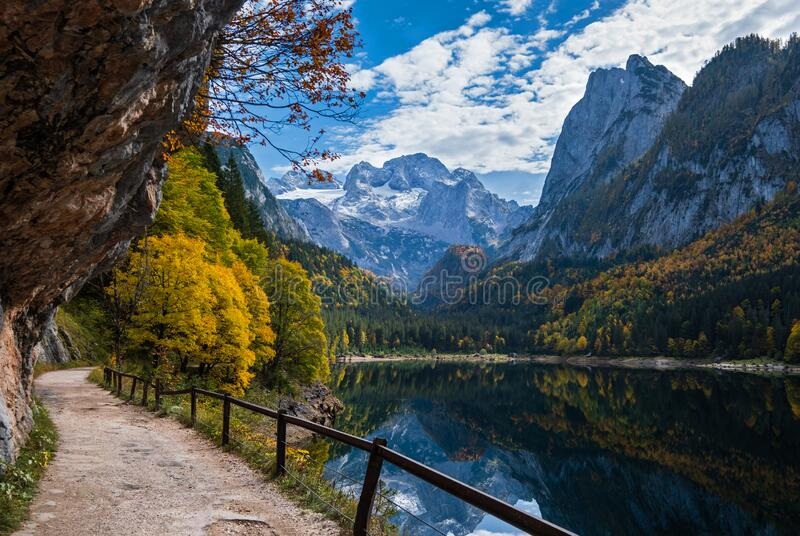 Peaceful autumn Alps mountain lake with clear transparent water and reflections. Gosauseen or Vorderer Gosausee lake, Upper. Sunny idyllic colorful autumn alpine royalty free stock photography