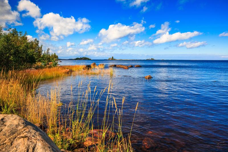 Sunny lake landscape in rural Finland royalty free stock photos
