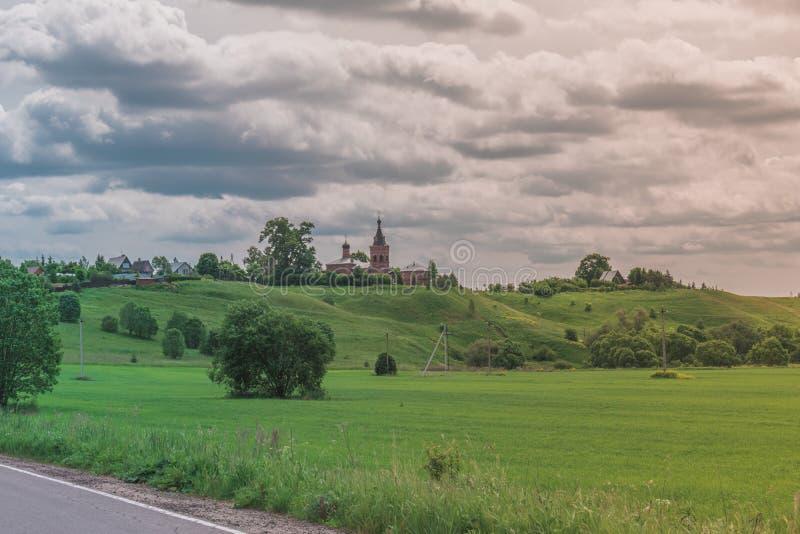 Sunny Landscape brilhante colorido com a igreja ortodoxo do russo no monte em um meio da foto com um céu nebuloso do contraste br imagem de stock