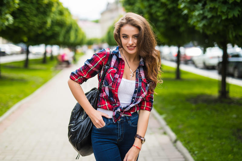 Sunny lifestyle fashion portrait of young stylish hipster woman walking on the street stock photography