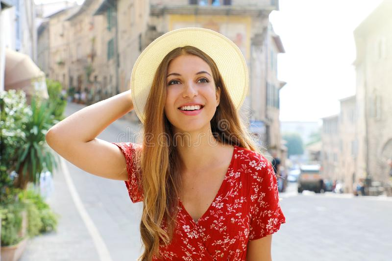 Sunny lifestyle fashion portrait of young  woman walking on the street with red dress and hat. Traveling in Italy stock photos
