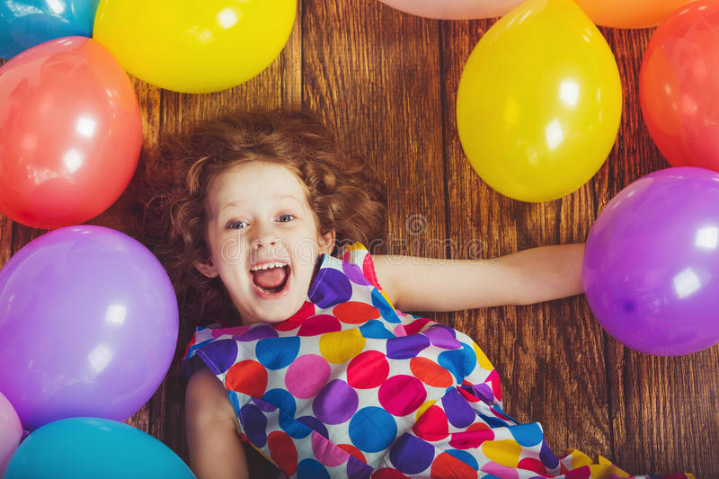 Sunny little girl in birthday party lying on wooden floor. With rainbow balloons. Happy childhood concept royalty free stock photo