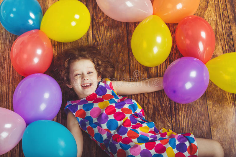 Sunny little girl in birthday party lying on wooden floor. With rainbow balloons. Happy childhood concept stock images