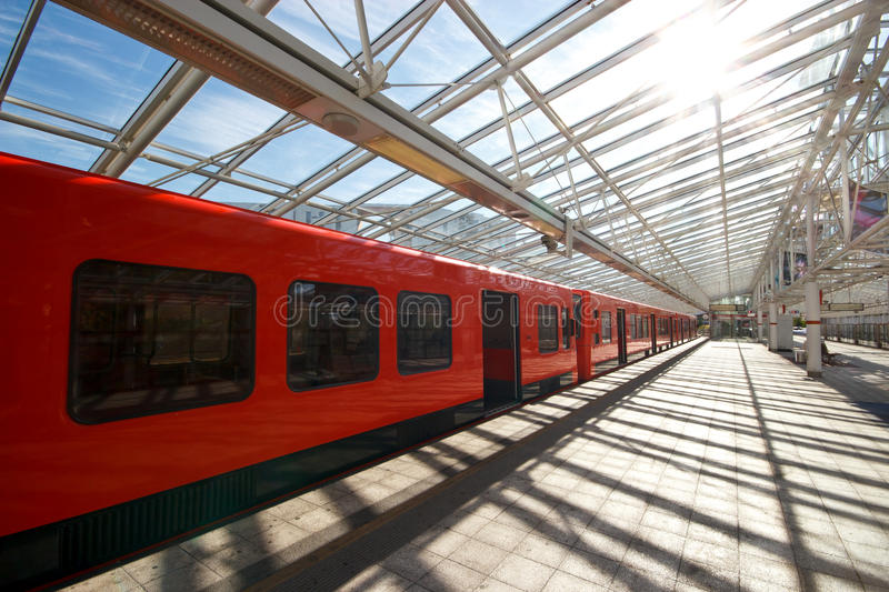 Sunny metro station. Sun shines trough the transparent roof of metro station with subway train stock images