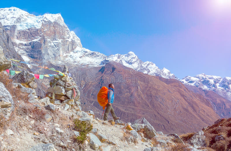 Sunny Mountain View and Nepalese Mountain Guide staying on Footpath. Sunny View of Himalaya Mountains and Nepalese professional Guide in blue Jacket staying on stock image