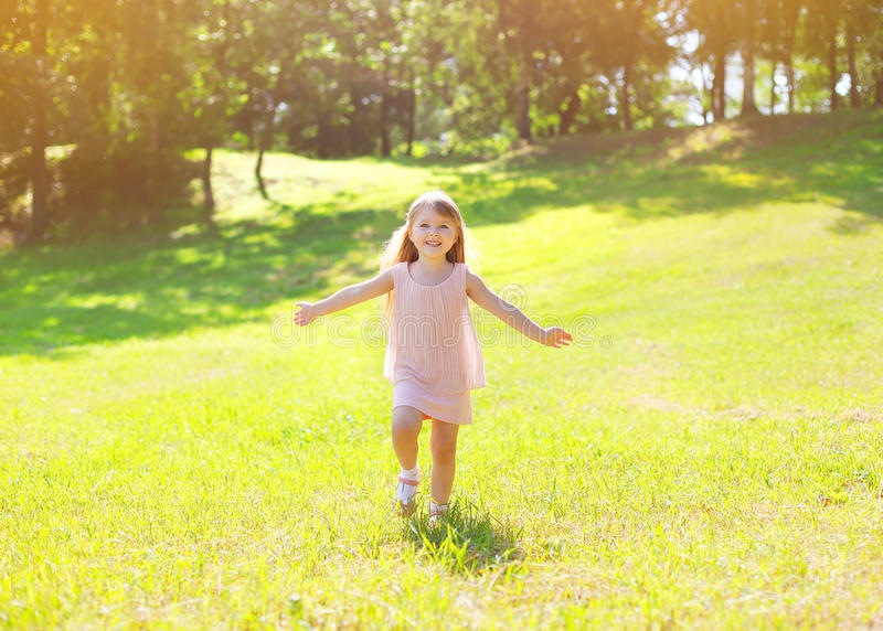 Sunny photo happy little child enjoying summer day. And having fun runs in field outdoors stock image