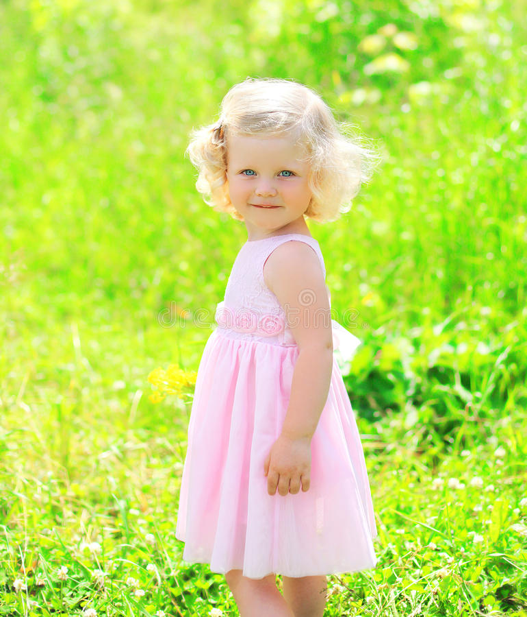 Sunny portrait of little girl child in dress on the grass. Summer royalty free stock photo