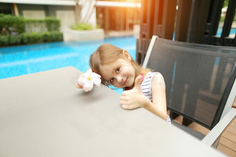 Sunny portrait of little kid girl showing thumbs up or like on swimming pool royalty free stock photo