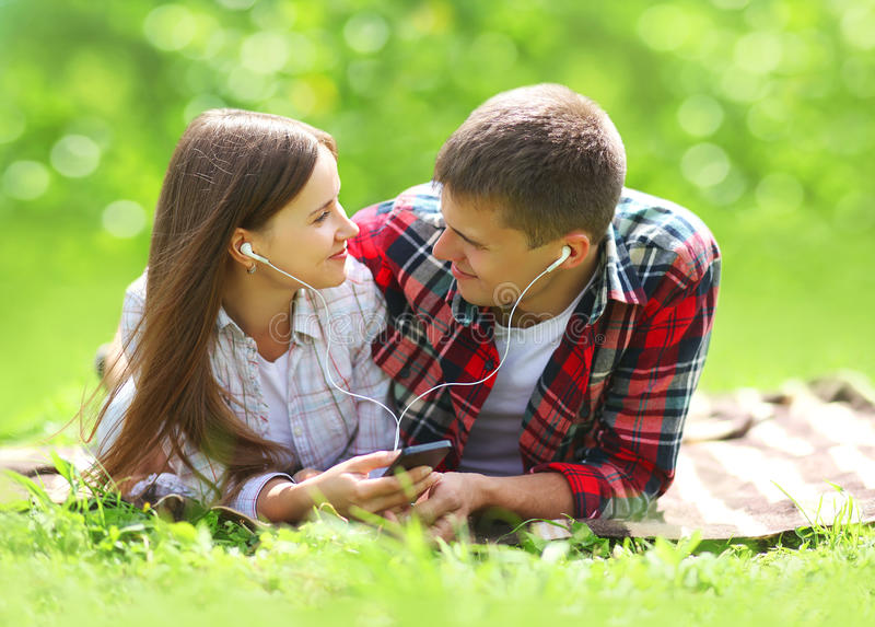 Sunny portrait of sweet young couple lying relaxing on the grass stock photos
