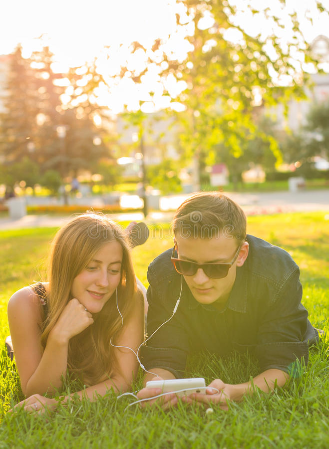 Sunny portrait of sweet young couple lying relaxing on the grass together listens to music in earphones on smartphone stock image