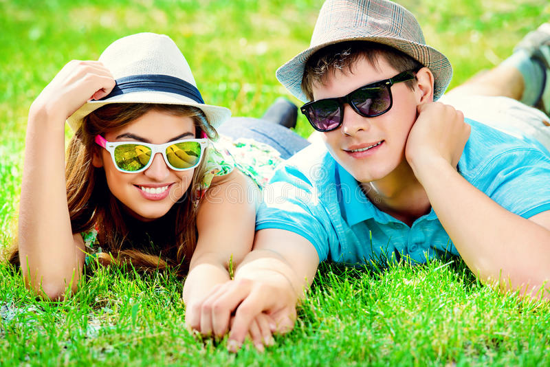 Sunny relations. Happy young couple relaxing on the lawn in a summer park. Love concept. Vacation royalty free stock image