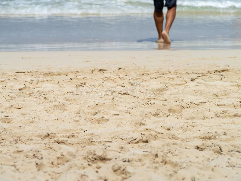 Low section of barefoot man walking into the waves on a sandy beach royalty free stock images