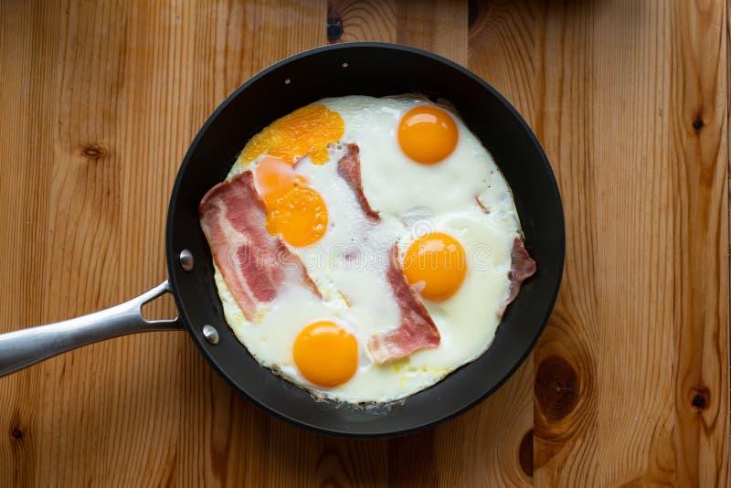 Sunny Side Up Eggs avec le lard, dans une casserole images libres de droits