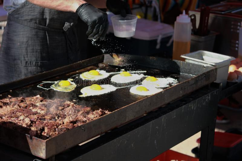 Sunny side up eggs salted beside steak on griddle royalty free stock photos