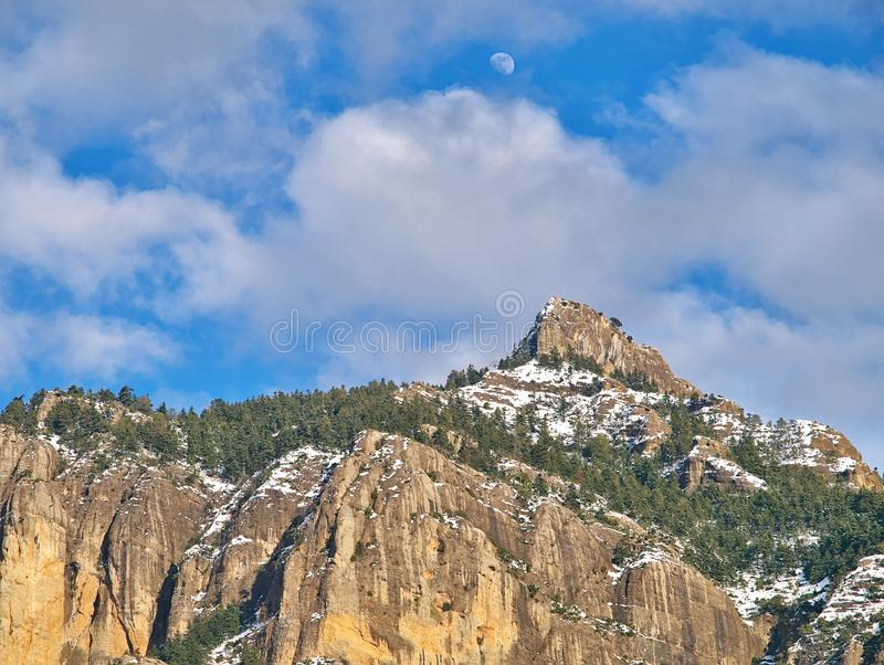 Sunny sky with some clouds and moon, over rocky mountain with trees and some snow. Corinthia, Greece royalty free stock images