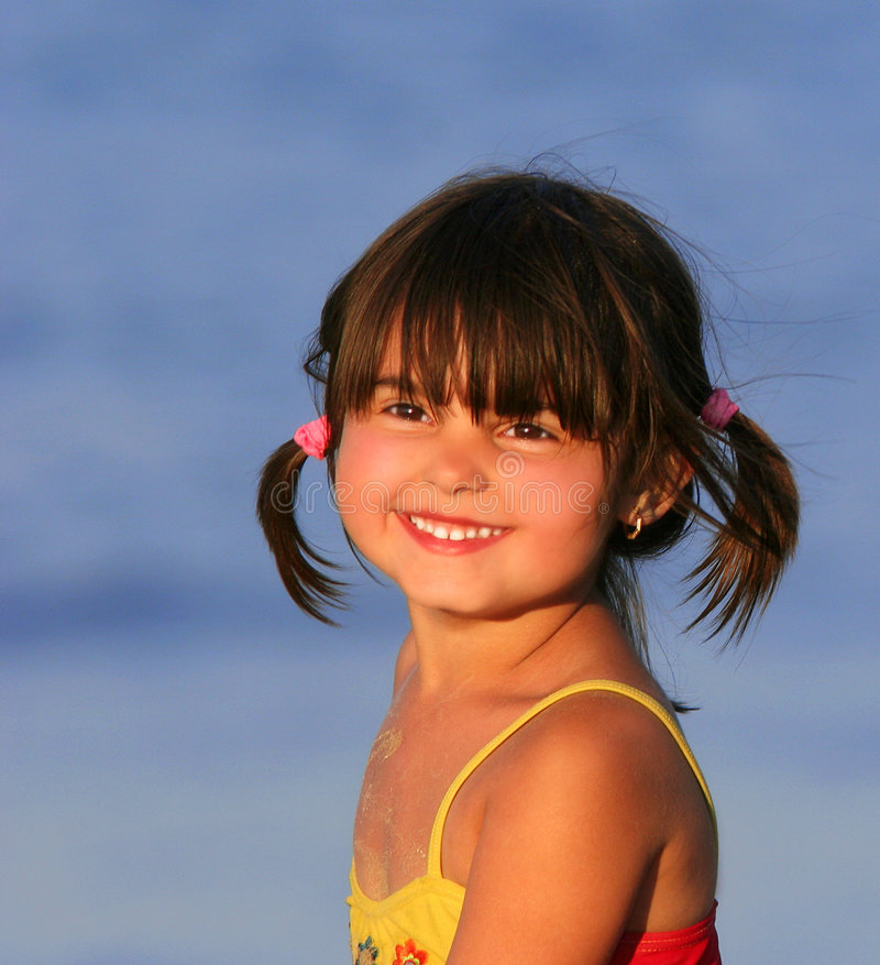 Sunny Smile. Little girl smiling at the beach in summer, wearing a red and yellow swimming costume and with her hair in pigtails