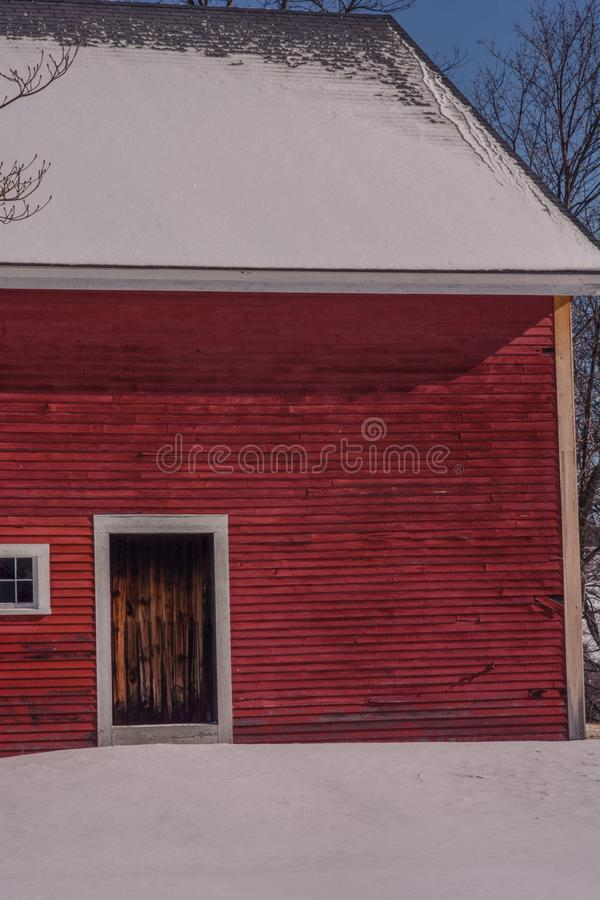 Brown barn door against the bright red clapboards against a snowy white field on a bright winters day. royalty free stock images