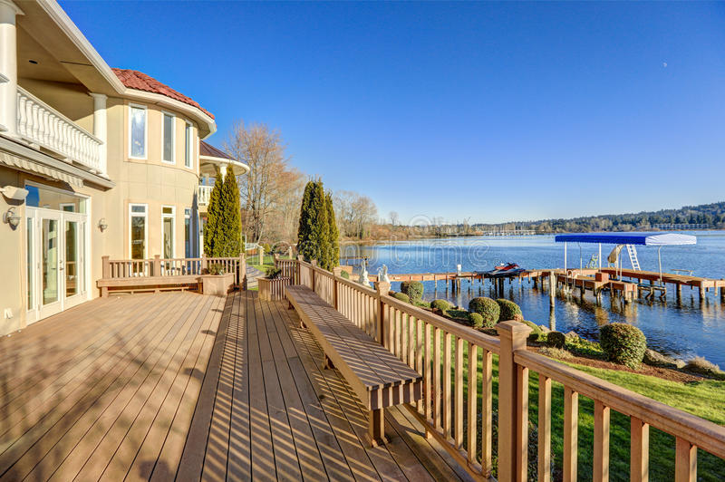 Sunny spacious walkout deck of luxurious waterfront home stock images