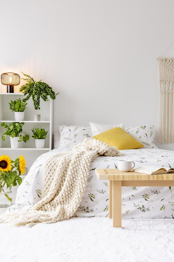 Sunny spring bedroom interior with green plants beside a bed dressed in eco cotton linen. Yellow accents. Empty white background wall. Real photo stock image