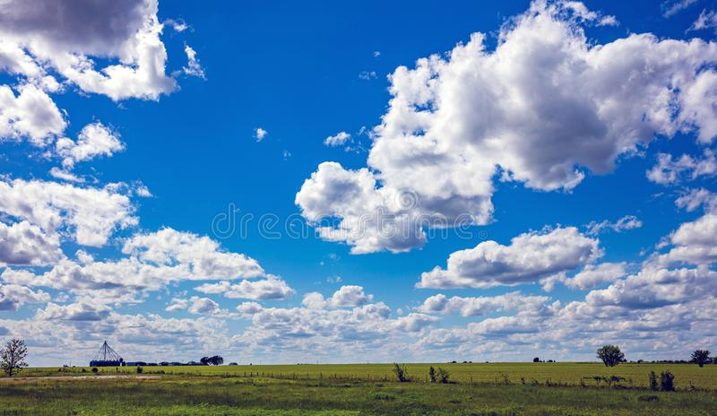 Sunny spring day in countryside. Green grass field, blue sky with clouds royalty free stock photography