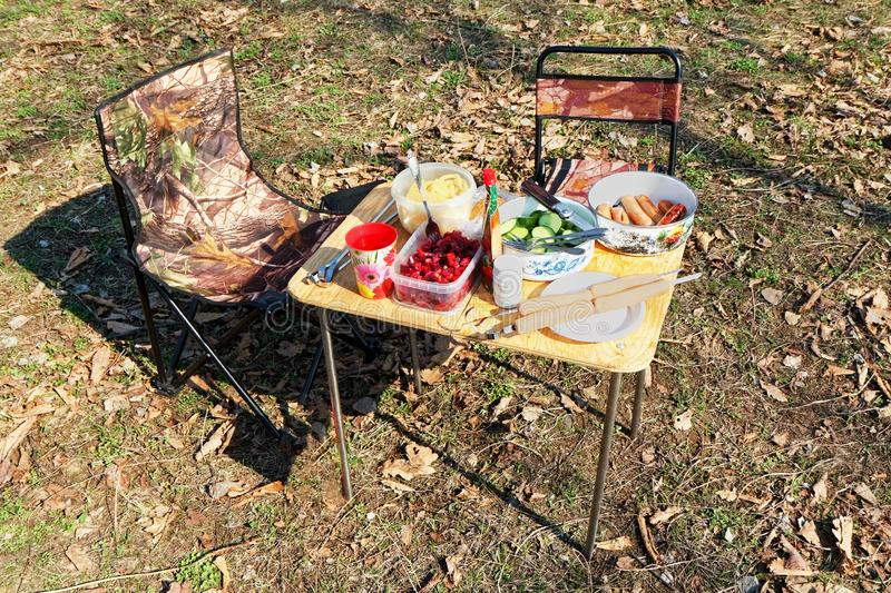 A table with food and two chairs for a picnic in the forest royalty free stock photos