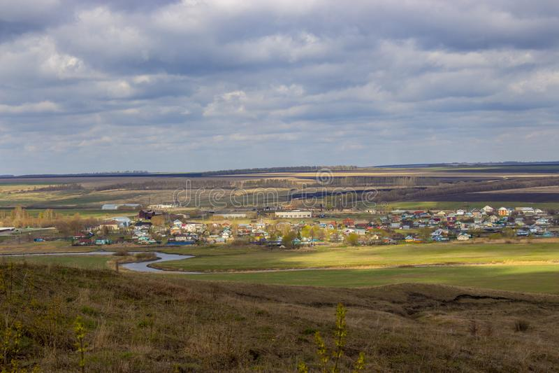 Sunny spring landscape Tatar village Russia. Multi-colored country houses under bright cloudy sky in the rays of sun. Sunny spring landscape Tatar village Russia royalty free stock image