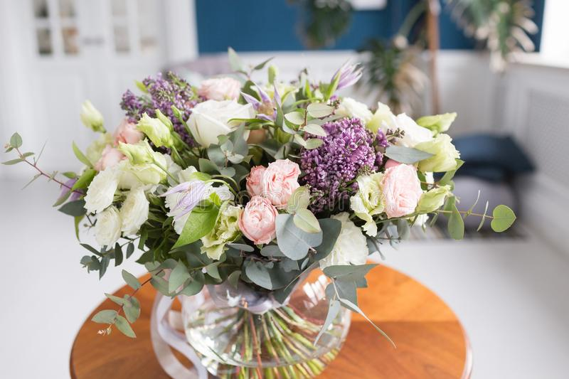 Sunny spring morning in living room. Beautiful luxury bouquet of mixed flowers in glass vase on wooden table. the work royalty free stock image