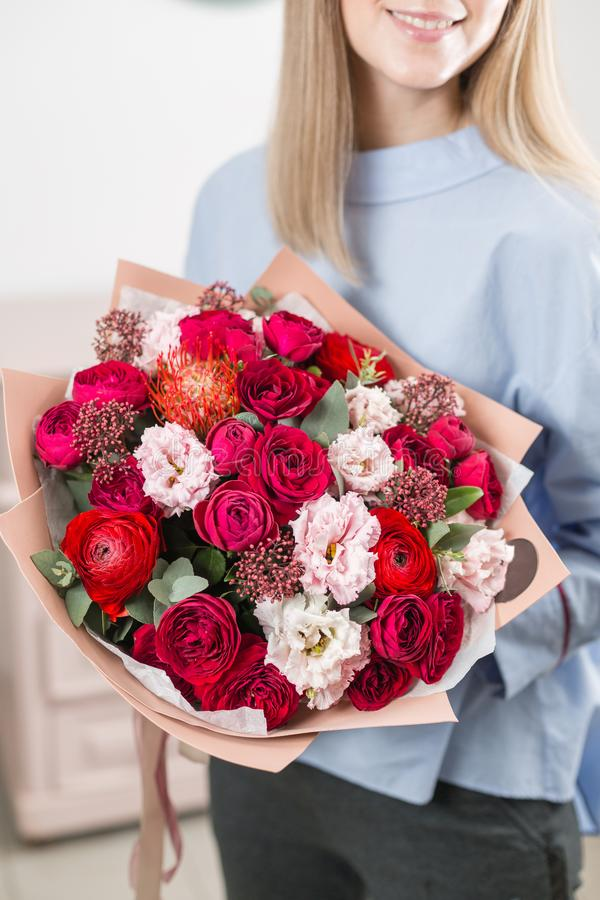 Sunny spring morning. Young happy woman holding a beautiful luxury bouquet of mixed flowers. the work of the florist at. A flower shop stock image
