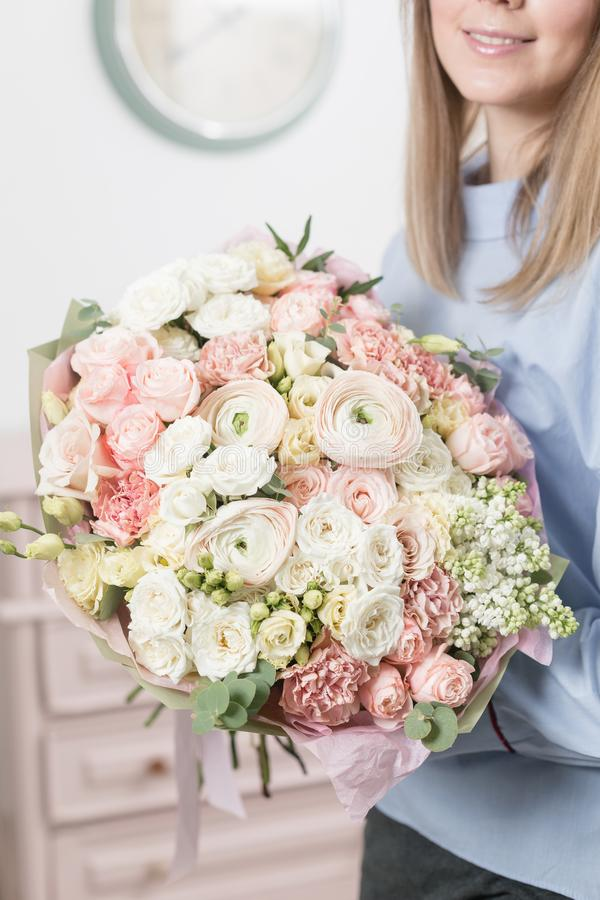 Sunny spring morning. Young happy woman holding a beautiful luxury bouquet of mixed flowers. the work of the florist at. A flower shop royalty free stock photo