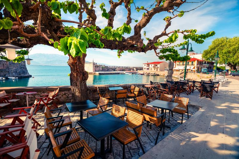 Sunny spring scene of the outdoor cafe in Nafpaktos town. Fantastic morning scene of the Gulf of Corinth, Greece, Europe. Traveling concept background stock photography