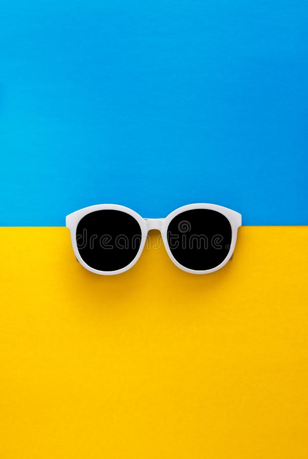Sunny stylish white sunglasses on a bright blue-cyan and yellow-orange background, top view, isolated. Copy space. Flat lay.  stock photo