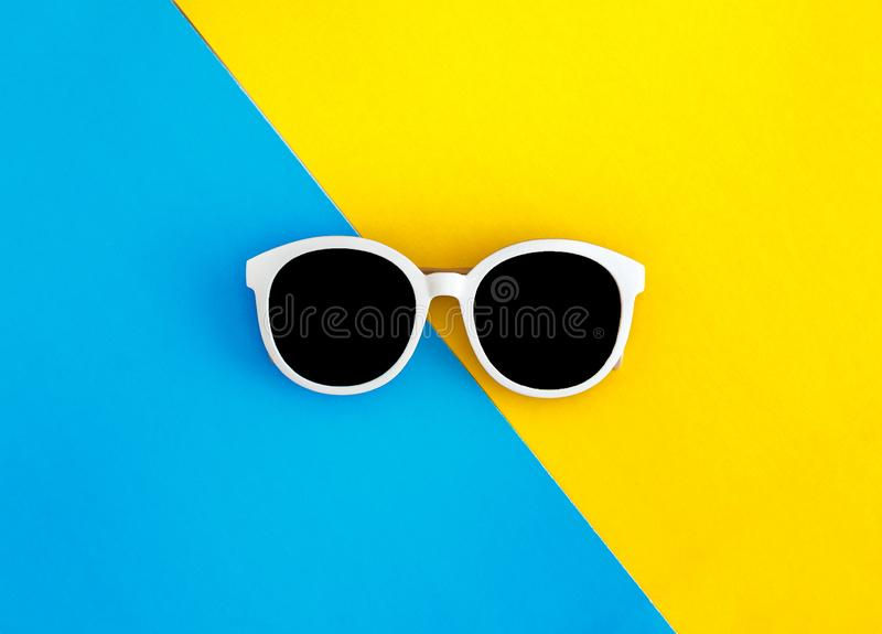 Sunny stylish white sunglasses on a bright blue-cyan and yellow-orange background, top view, isolated. Copy space. Flat lay.  royalty free stock image